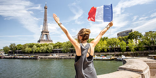 Waving a French flag in front of the Eiffel Tower