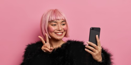Lady with pink hair posing with camera phone
